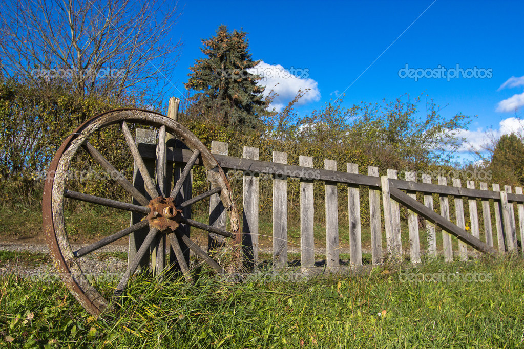 Old wheel and wooden fence