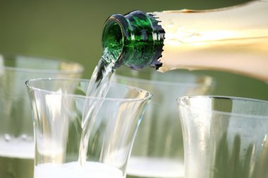 Close-up of bottle and pouring sparkling wine.
