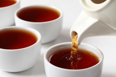 Tea cups and pouring black tea.