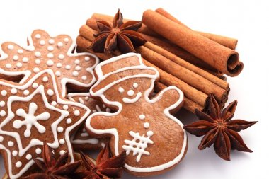 Gingerbread cookies and spices for Christmas baking on white background.