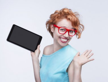 Emotional cute red-haired girl holding tablet computer, opening hands.