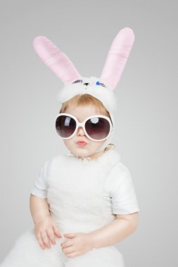 Boy wearing a bunny rabbit costume and sunglasses. Kiss lips. Studio shot gray background. 2 year white easter rabbit