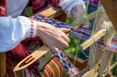 Woman working at the weaving loom. Traditional Ethnic craft of Baltic.