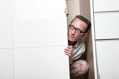 Concerned man look out white wardrobe