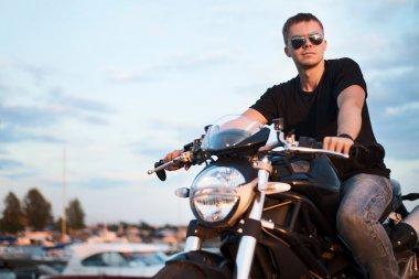 Romantic portrait handsome biker man in sunglasses sits on a bike on a sunset near lake