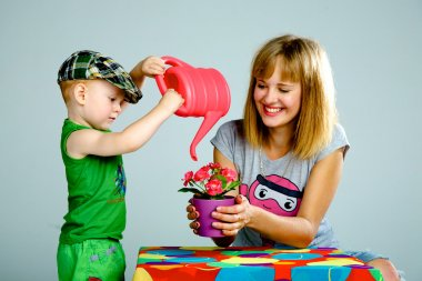 Mom and son watering flowers with a watering can
