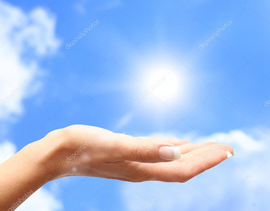 Sun on human hand against blue sky.