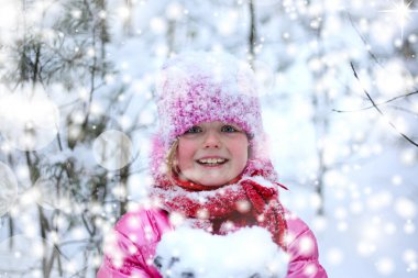Little girl in winter pink hat in snow forest.