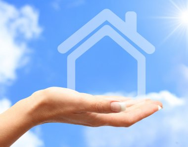 Abstract house in women hand against blue sky
