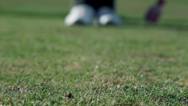 Schuss ein Golfer gehen auf einen Punkt, wo er einen weißen Golfball auf den speziellen Halter klebt, hautnah