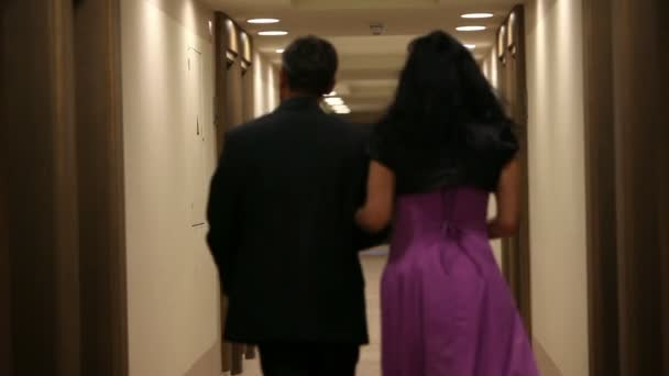 3822c3708912 Couple dressed in evening wear walking down the hotel corridor– stock  footage