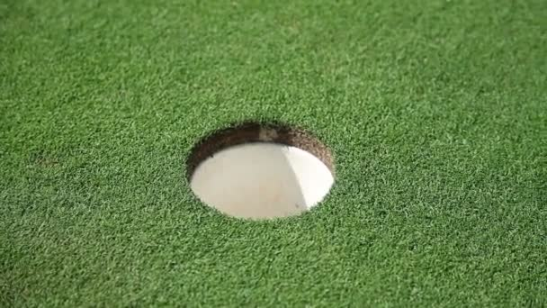 Close up shot of a hall and white golf ball that goes directly to the hall and a golfers hand that picks up a golf ball