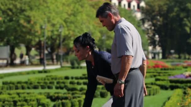 starší pár, užívat si volného času v parku a shromažďování krásné květiny