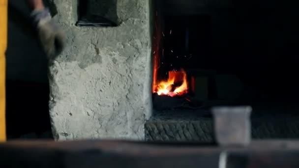 Schmied bläst Luft in den Ofen, um Funken zu bekommen