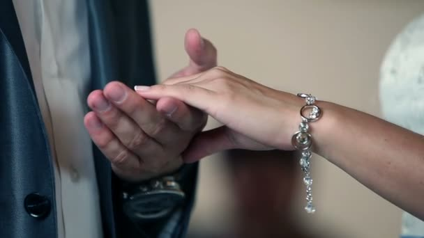Bride and groom hand exchanging gold wedding rings on a wedding ceremony