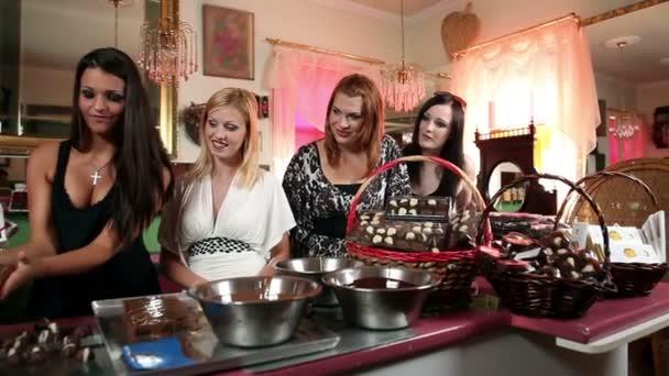 Aufnahme von vier Freundinnen, die eine gute Zeit haben, während sie Schokolade herstellen