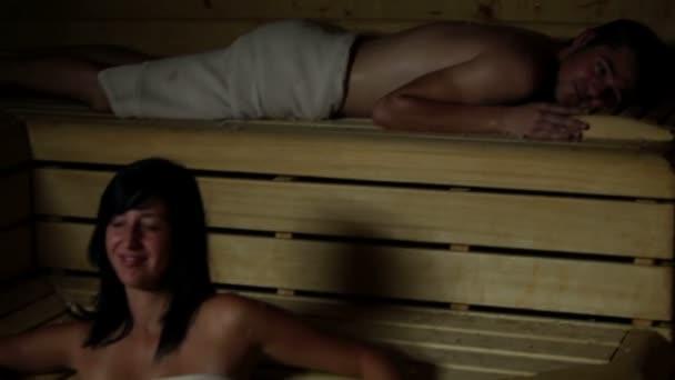 mladá žena uvolňující a směje se v sauně
