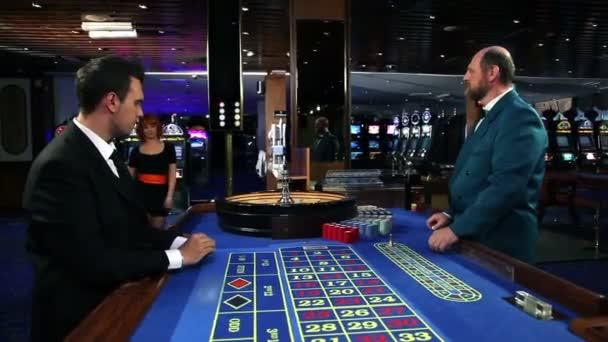 mladí coople flirtování a hraní rulety v kasinu
