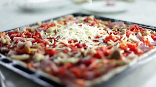 zblízka střílel černý plech s těsta a osoba, která je uvedení na různé druhy ingredience na pizzu