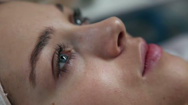 mladá žena leží v salonu krásy a při pohledu přímo ve fotoaparátu