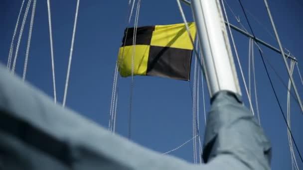 detail mává černé, žluté vlajky na plachetnici