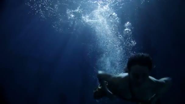 Žena, plavání pod vodou v dlouhých žlutých šatech