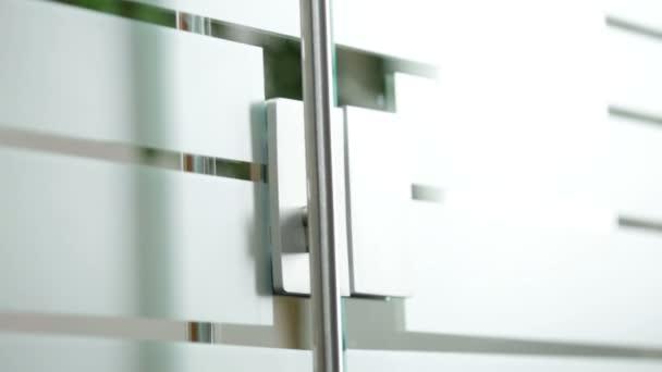 Žena, otevírání skleněných dveří do kanceláře