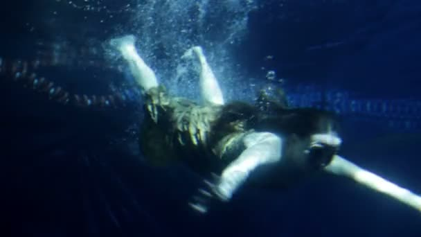 Woman swimming under water in long yellow dress