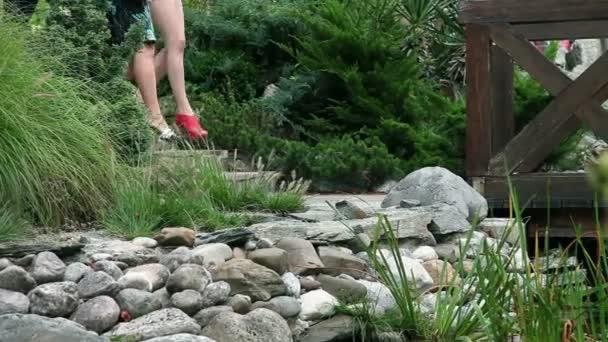 Nahaufnahme Shot auf Frauen Beine mit Heels zu Fuß über eine Holzbrücke