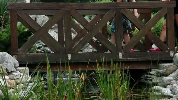 Close up shot on women legs with heels walking over a wooden bridge