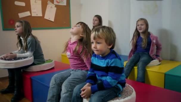 děti ve školce seřazeny na lavičce