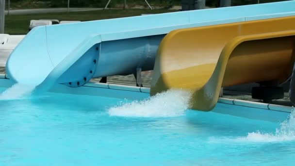 Colorful water slides in pool with people sliding down