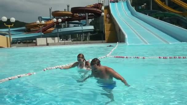 Young couple going out the pool with waterslide