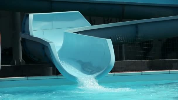 Close up on three kids going down the waterslide