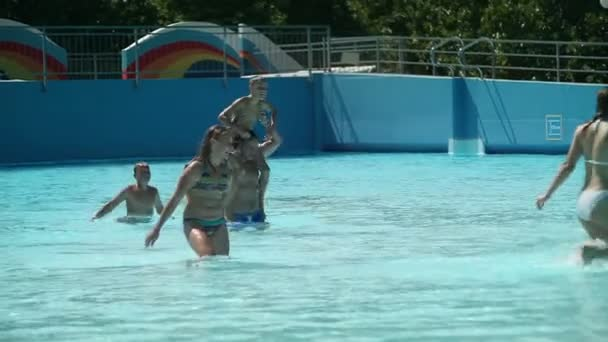 Group of people having fun in pool and playing with ball