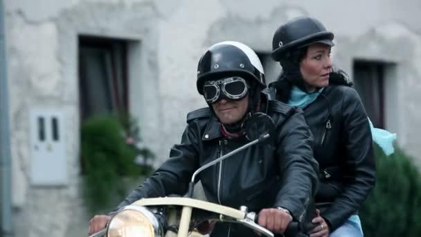 po pár středního věku o staré motorce projíždí městem
