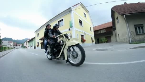 Middle aged couple driving on old motorcycle in small town