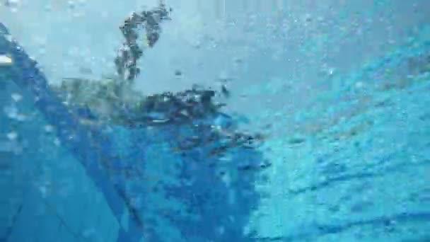 Pool underwater shot of boy jumping on head