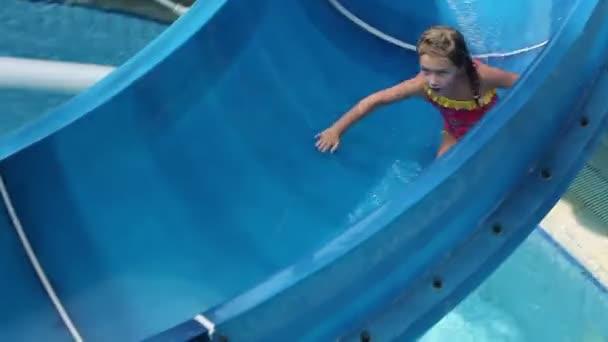Mädchen im Rosa Badeanzug und jungen rutschen die Wasserrutsche
