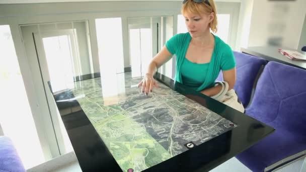 žena zkoumání mapu na dotykové obrazovce stůl