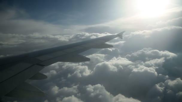 obrovské křídlo cestující letadla při letu nad mraky