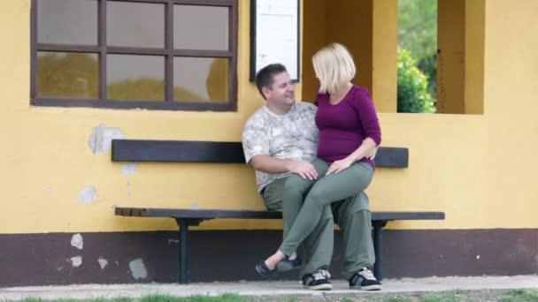 těhotná žena, sedící v klíně přítele, zatímco ukazuje zhodnocení