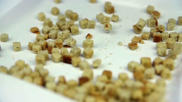 Kleine Brotstücke fallen in Zeitlupe auf spiegelnde Oberfläche