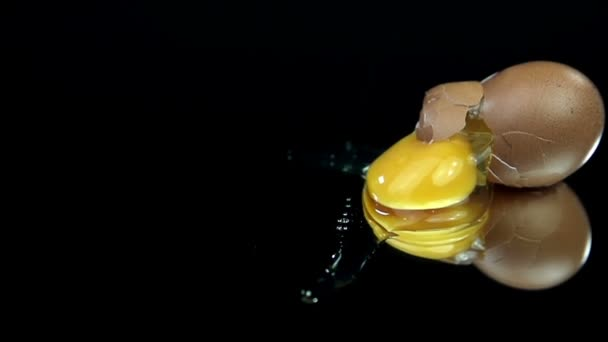 Ei fällt, zerbricht und verschüttet auf schwarzem Hintergrund