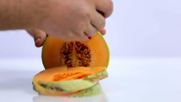 Piercing Melone mit violettem Stroh auf weißem Hintergrund