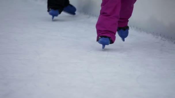 Blaue Kinderschlittschuhe taumeln auf der Eisbahn