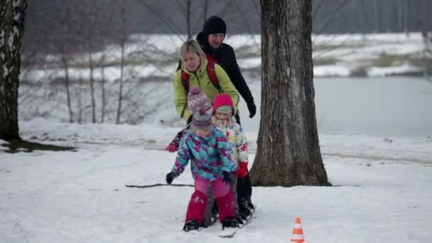 Familie versucht auf großen Skiern zu laufen, als Kind stürzt
