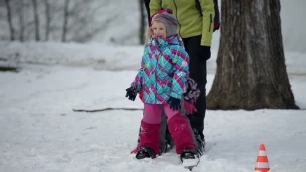 Kinder lächeln und fallen spielerisch nacheinander, wenn Familie auf großen Skiern spazieren geht