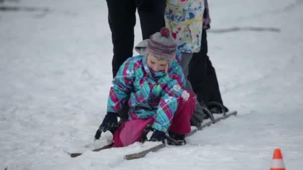 Kind steht auf, um mit der Familie auf Holzskiern zu laufen