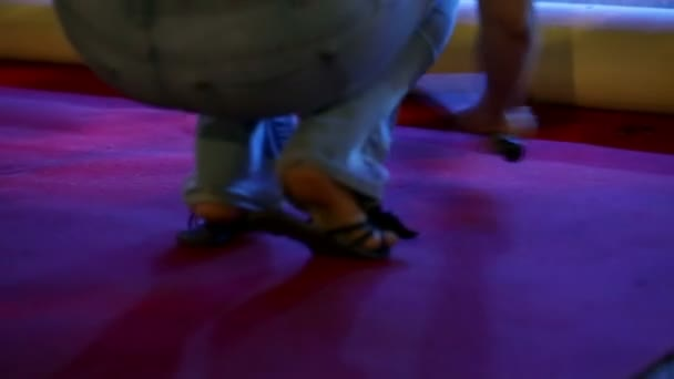 Woman is cleaning the red carpet squating in her jeans